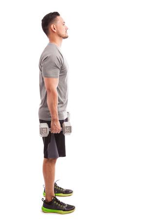 profil: Profil widok młodego mężczyzny w stroju sportowym o podnieść niektórych wag na białym tle