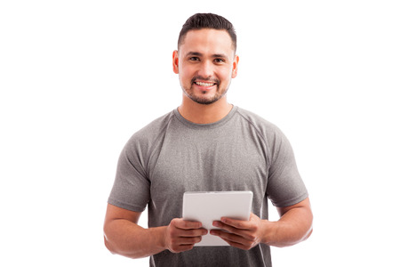 Attractive young fitness coach using a tablet computer on a white background