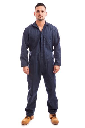 Full length portret van een jonge goed uitziende man het dragen van overalls voor het werk op een witte achtergrond