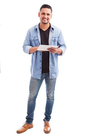 white man: Portrait of a good looking Hispanic young man dressed casually social networking on a tablet computer and smiling Stock Photo