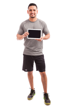 coaches: Handsome athletic man showing the screen of a tablet computer with the latest fitness app