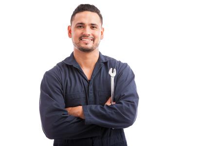 Portret van een jonge monteur die een moersleutel en glimlachend, klaar om auto's te repareren