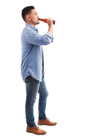흰색 배경에 대해 병에서 젊은 히스패닉 남자 마시는 맥주의 전체 길이 프로필보기