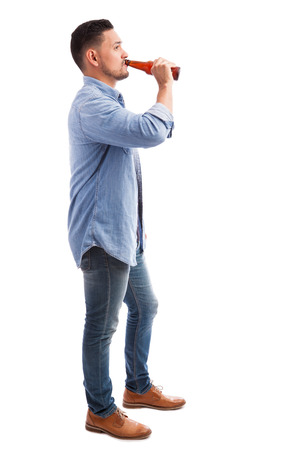 In voller Länge Profilansicht eines jungen hispanischen Mann trinkt Bier aus einer Flasche vor einem weißen Hintergrund