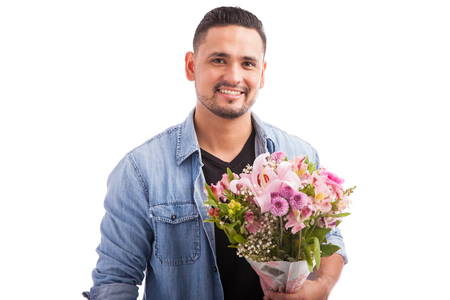 background person: Good looking Latin guy holding a bunch of pink flowers and getting ready to meet his date for dinner