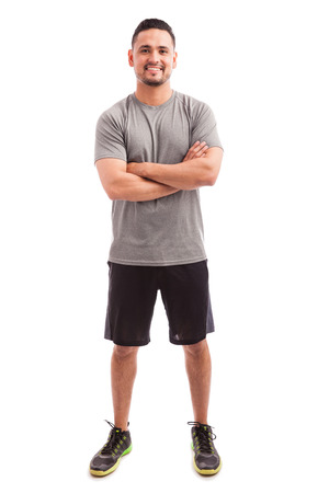fitness hombres: el preparador f�sico hispano de sexo masculino con los brazos cruzados y sonriente sobre un fondo blanco