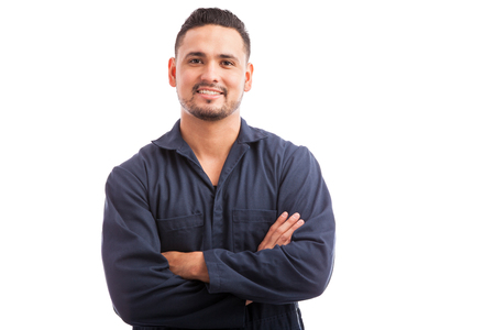 Young Hispanic mechanic wearing overalls and smiling with his arms crossed