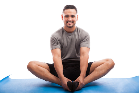 Good looking Latin guy sitting on a yoga mat and doing some stretching exercises on a white background