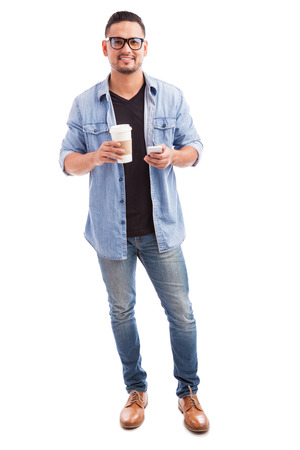 Full length portrait of a handsome hipster man drinking coffee and using a smartphone on a white background