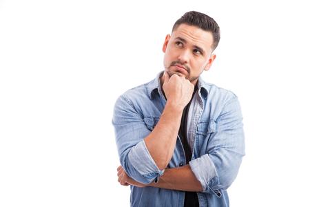 persona pensando: Retrato de un hombre joven y guapo mirando hacia arriba y pensar con fuerza contra un fondo blanco Foto de archivo