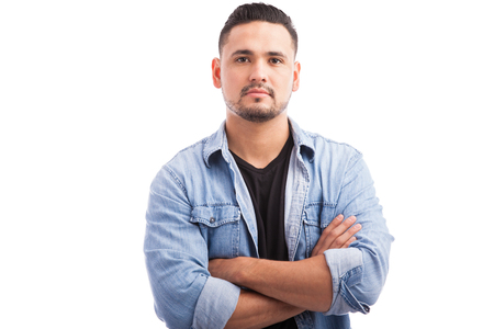 Portret van een zelfverzekerde jonge man met zijn armen gekruist tegen een witte achtergrond