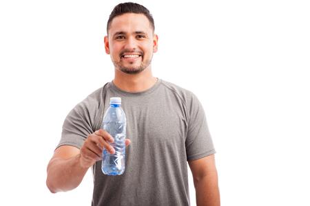 mamadera: Retrato de un hombre joven en traje deportivo que ofrece una botella de agua a la c�mara y sonriendo