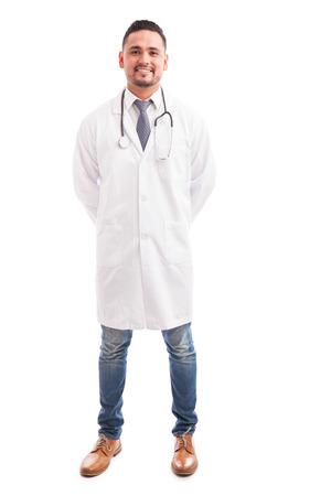 bata blanca: Retrato de cuerpo entero de un médico varón joven con una bata de laboratorio y un estetoscopio sobre un fondo blanco