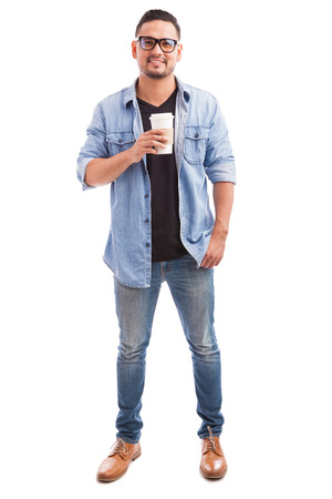 on a white background: Portrait of a young hipster man wearing glasses and drinking coffee from a cup in a white background Stock Photo