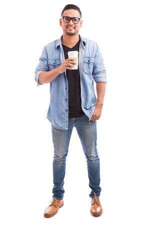 persona de pie: Retrato de un hombre inconformista joven con gafas y bebiendo café de una taza en un fondo blanco