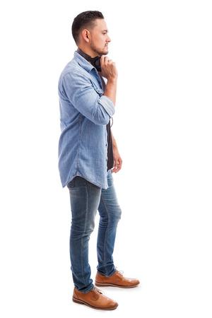 Vista di profilo di un giovane uomo latino che indossa le cuffie e ascoltare musica su uno sfondo bianco Archivio Fotografico - 47228922
