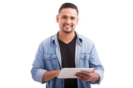 Portrait eines attraktiven jungen Mann lässig gekleidet mit einem Tablet PC und in einem weißen Hintergrund lächelnd