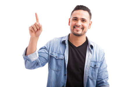 Young Latin man in dressed casually pointing and looking up towards copy space