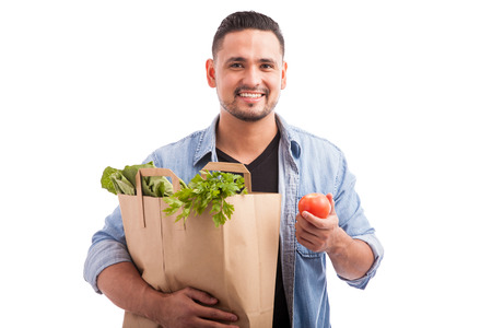 healthy looking: Good looking Latin man carrying a bag of groceries and showing all the healthy food he just bought Stock Photo