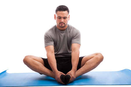 man sit: Young man sitting on an exercise mat and stretching his legs on a white background