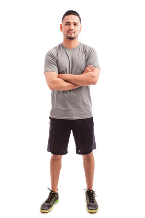 eye contact: Good looking young fitness instructor standing with his arms crossed and making eye contact Stock Photo