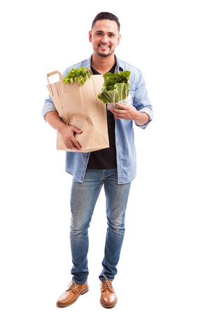 abarrotes: Full length view of a young man carrying a bag of groceries with lots of greens in it and smiling
