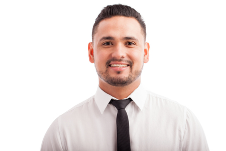business contact: Portrait of a good looking young Hispanic man wearing a tie and smiling against a white background Stock Photo
