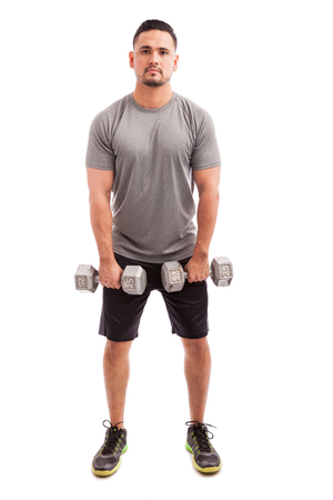 strengthen: Young Hispanic man in sporty outfit raising dumbbells to strengthen his deltoids on a white background