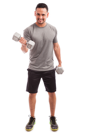 curls: Full length portrait of a young attractive man doing bicep curls with a couple of dumbbells Stock Photo