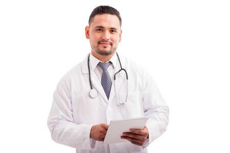 bata blanca: Apuesto joven médico con una bata de laboratorio y un estetoscopio con un tablet PC para comprobar la historia de un paciente