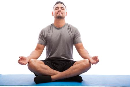 Jonge man in sportieve outfit doet yoga en mediteren op een oefening mat tegen een witte achtergrond Stockfoto