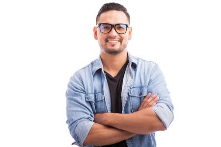 personen: Latin hipster man draagt een bril met zijn armen gekruist en lachend op een witte achtergrond