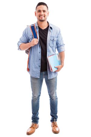 Ritratto integrale di un ragazzo ispanico che trasporta alcuni libri e uno zaino su uno sfondo bianco