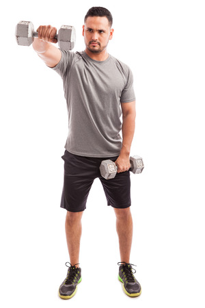 Full length view of a young man doing some deltoid raises with a couple of dumbbells on a white background