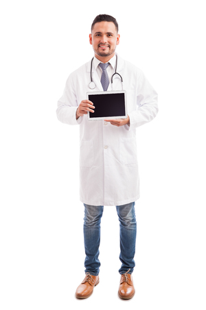 Full length view of a young doctor showing the screen of a tablet computer against a white background Stock Photo