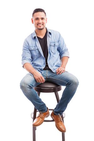 silla: joven atractiva vestida casualmente sentado en una silla y sonriente sobre un fondo blanco