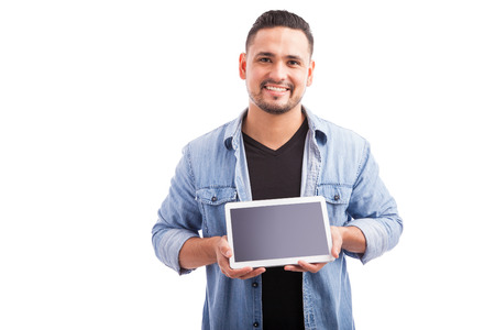 tablet: Good looking young man showing the screen of a tablet computer and smiling Stock Photo