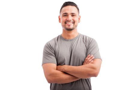 hombre deportista: Apuesto atleta América con un traje deportivo con los brazos cruzados y sonriente sobre un fondo blanco