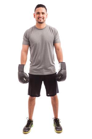 fitness hombres: Retrato de un hombre latino joven en traje deportivo y el uso de guantes de boxeo listos para la práctica y la sonrisa