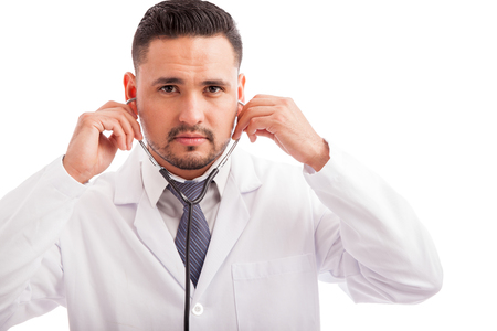 good looking: Portrait of a good looking young Latin doctor putting his stethoscope on before examining a patient Stock Photo