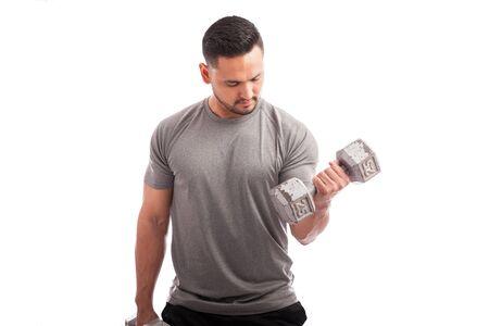 pesas: Hombre apto de los jóvenes levantar algunas pesas y trabajar en su bíceps sobre un fondo blanco