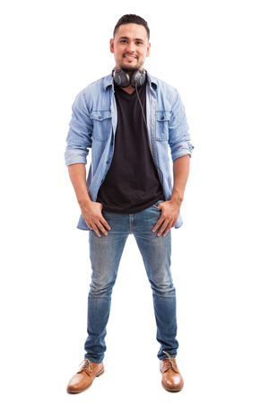 Full length portrait of a young man dressed casually and wearing headphones in a white background