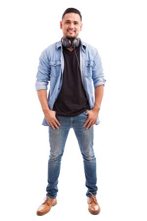auriculares: Retrato de cuerpo entero de un hombre joven, vestido casualmente y el uso de auriculares en un fondo blanco Foto de archivo
