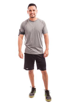 fitness hombres: Vista de la longitud completa de un hombre joven en traje deportivo listo para comenzar su entrenamiento de escuchar un poco de música
