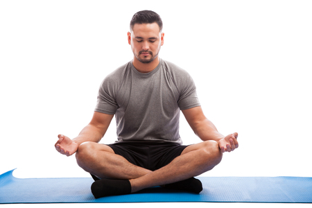 Portrait of a young man sitting on a yoga mat and doing some meditation with his eyes closed