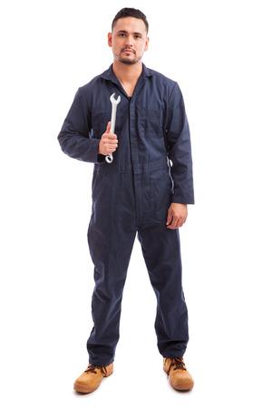 bonhomme blanc: Portrait d'un jeune m�canicien salopette et tenant une cl� au travail sur un fond blanc