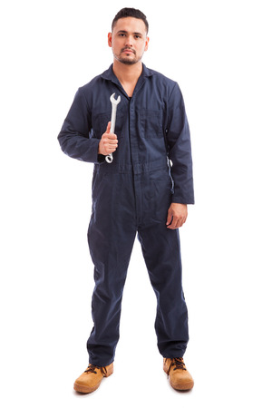 white people: Portrait of a young mechanic wearing overalls and holding a wrench at work on a white background Stock Photo