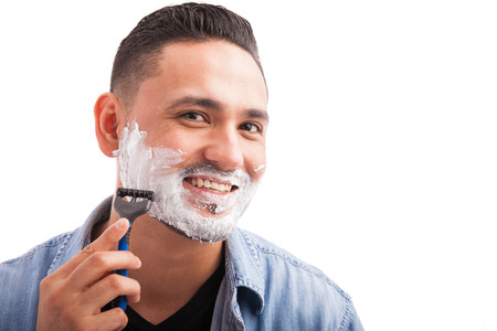 good grooming: Portrait of a handsome man with shaving cream on his face and using a razor to shave Stock Photo