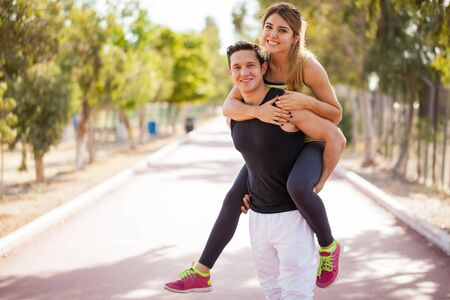 Handsome young man giving a piggyback ride to his girlfriend Stok Fotoğraf