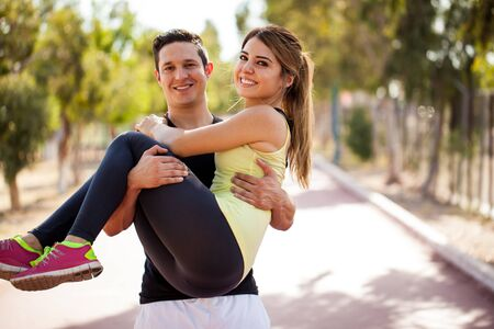 Portrait of a cute happy girl being carried by her boyfriend while they both exercise at a running track